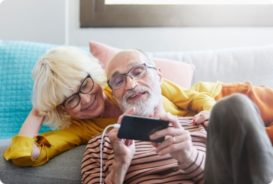 A man and woman smiling watching something on his phone