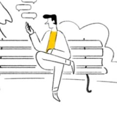 A man sat on a bench whilst texting