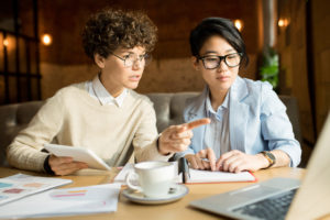 Serious pensive young marketers in glasses sitting at table and discussing strategy: curly-haired lady offering idea and pointing at laptop screen