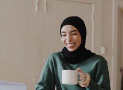 woman smiling looking at computer screen